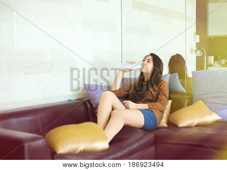 Biracial teen girl or young woman sitting on black leather sofa drinking bottled water with sunlight streaming from window