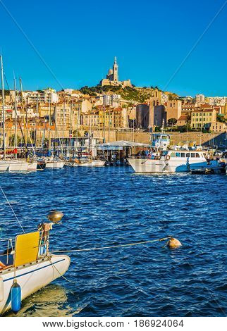 The water area of the Old Port - yachts, speedboats and fishing boats. On the hill - splendid Basilica of Notre-Dame de la Garde. Marseilles