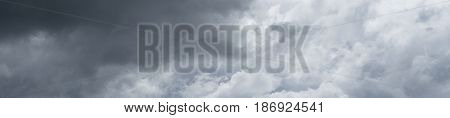 Panorama of rainy clouds flying over horizon. Dramatic cloudy sky.