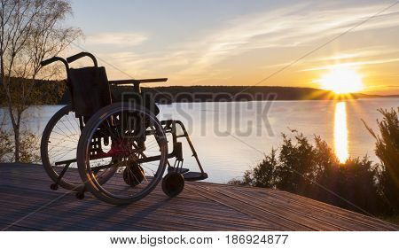Empty wheelchair standing in a park at sunset