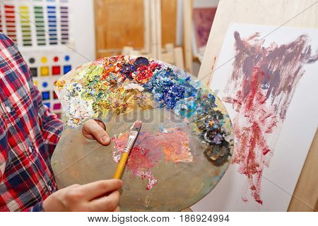 Man mixes oil paints on a wooden palette. He holds a flat brush of bristles. A lesson in art school. Courses of drawing for adults.