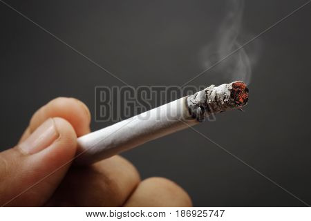 Smokers hand with cigarette on dark background.