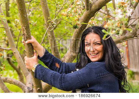 Happy woman in garden holding branch spring tree