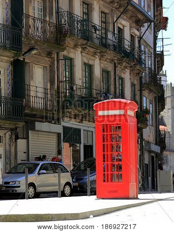 A red phone booth in the old town of Porto, Portugal.