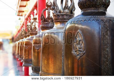 Closeup row of bells in buddhist temple in Thailand. Buddhist temple bells. Bells of the old temple in Thailand