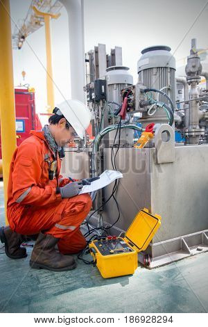 TechnicianInstrument technician on the job calibrate or function check pneumatic control valve in process oil and gas platform offshoretechnician