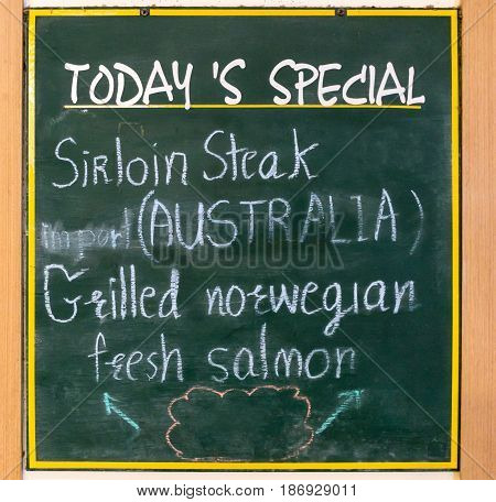 Advertising wooden sign stands in front of restaurant for today's special menu.