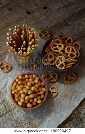 Salty Snacks On Wooden Background. Crackers, Pretzel, Salted Straws, Nuts, Dried Fish. Junk Food For