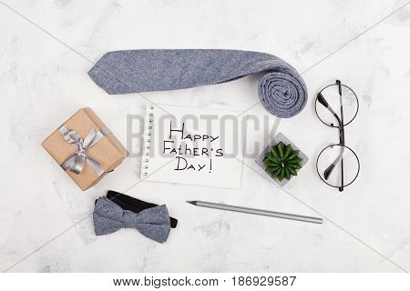Happy Fathers Day background with notebook gift glasses necktie and bowtie on white working desk top view in flat lay style.