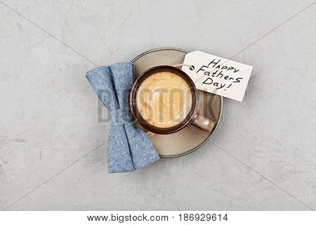 Morning cup of coffee and bowtie on stone desk top view in flat lay style for breakfast on Happy Fathers Day.