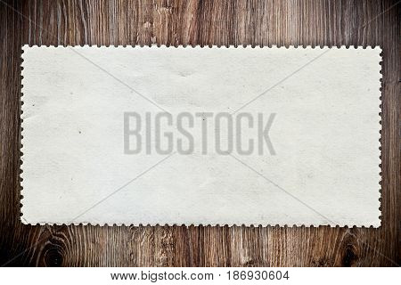 Photo of a blank post stamp on wooden background