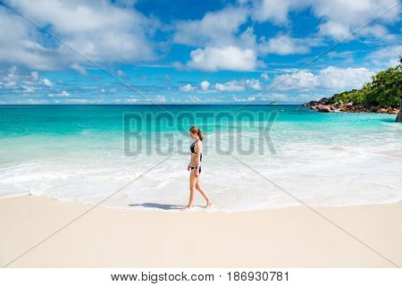 Photo of a young woman walking on the beach