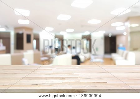 Wood table top on blur white room background - can be used as office or hospital lobby background
