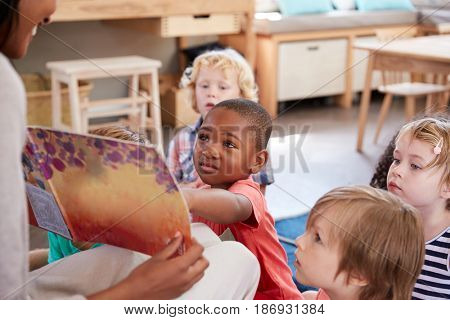 Pupils At Montessori School Looking At Book With Teacher