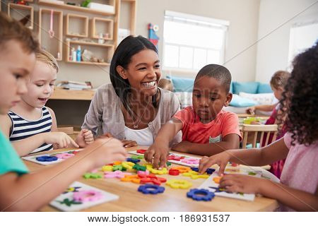 Teacher And Pupils Using Flower Shapes In Montessori School