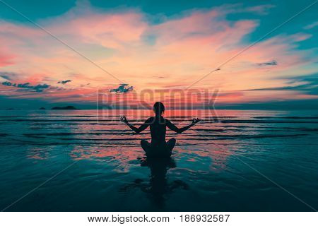 Yoga silhouette. Meditation girl on the sea during amazing sunset. Fitness and healthy lifestyle.