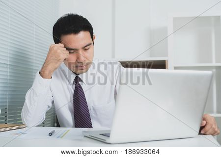 Asian businessman getting stressed at work in front of laptop computer - soft tone