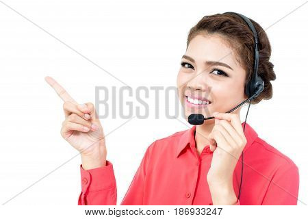 Young businesswoman wearing microphone headset as an operator pointing her hand to blank space