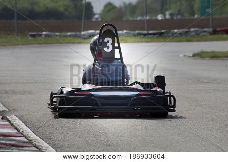 man drive go kart on track back view outdoor shot
