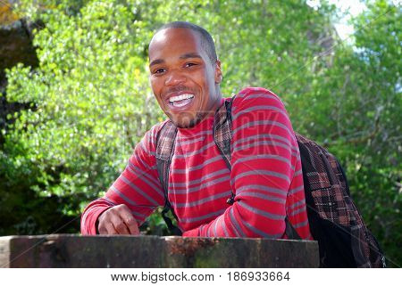 Young black male college student wearing a backpack sitting at an outdoor table