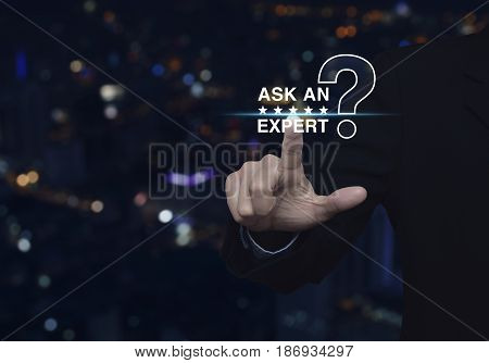 Businessman pressing ask an expert with star and question mark sign icon over blur colorful night light city tower