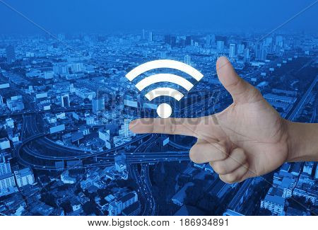 Wifi icon on finger over modern city tower street and expressway Technology and internet concept