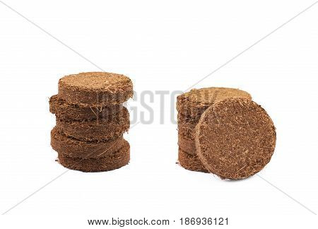 Pile of multiple compressed compost tablets, composition isolated over the white background, set of two different foreshortenings