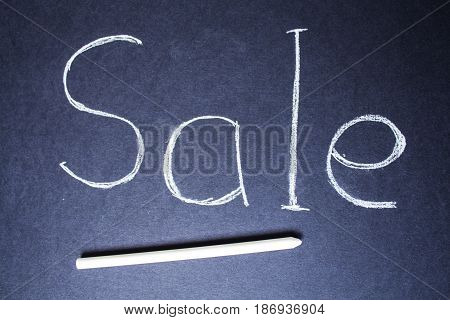 a Sale sign on blue chalk board with chalk