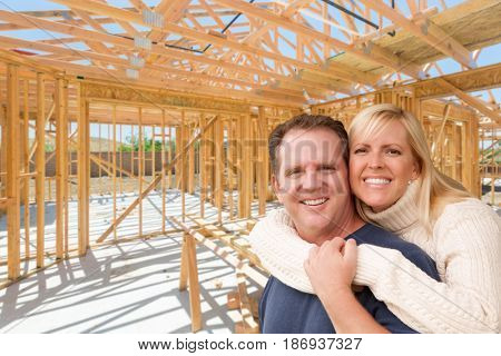 Happy Excited Couple On Site Inside Their New Home Construction Framing.
