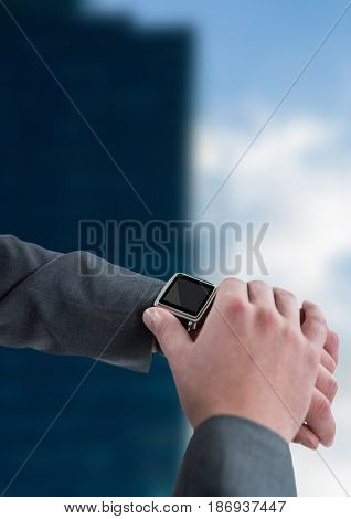 Digital composite of Hands with watch against blurry building