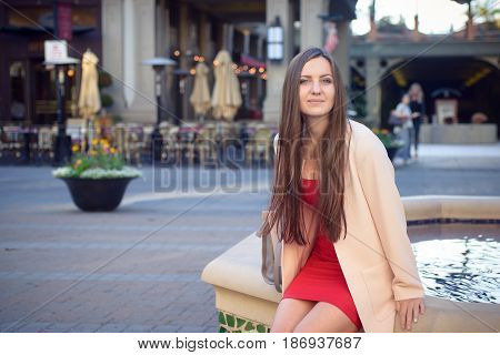 Young beautiful woman near cafe on the square in city street,