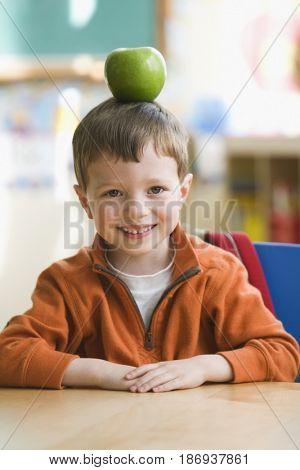 Caucasian boy balancing apple on his head