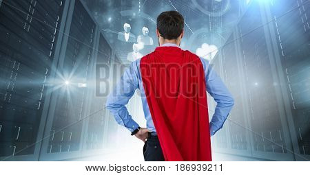 Digital composite of Back of business man superhero with hands on hips against servers with flares