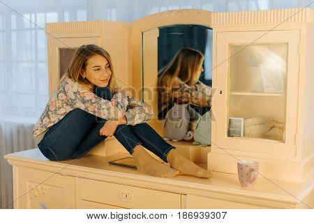 The smiling teenager is hugging her knees while sitting on the dressing-table