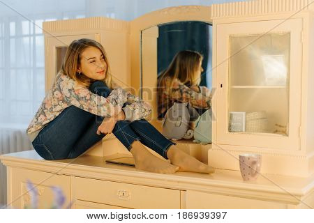 The dreaming blond teenager is hugging the knees while sitting on the dresser. The side view