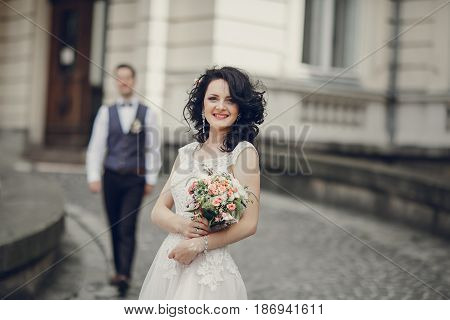 bride stands in the yard and in the background a big old house and groom