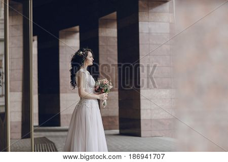 Bride stands at the high columns with a bouquet of flowers