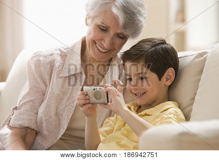 Caucasian grandmother and grandson looking at pictures on digital camera