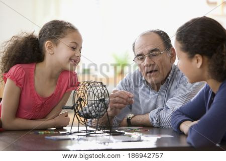 Hispanic girls and grandfather playing game