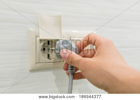 woman hand puts plug in the socket closeup shot. Hand Putting Plug Into Electricity Socket. Female hand unplugging