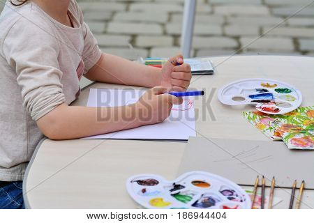 Little girl holds colorful crayons in her hand. Painter utensils on the table.