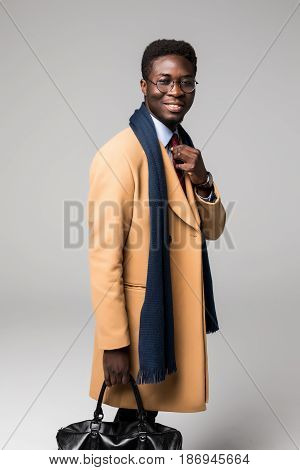 African Businessman In Coat Walking With Suitcase Before Travel Isolated On White
