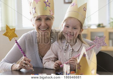 Caucasian grandmother and granddaughter doing arts and crafts together