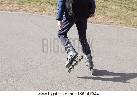 the person rides roller skates in the park in clear summer day