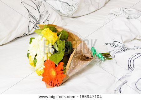 Bouquet of flowers over white bed in morning