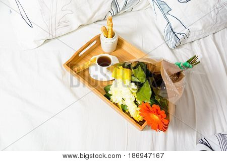 Breakfast With Coffee And Snack With Bouquet Of Flowers On Tray
