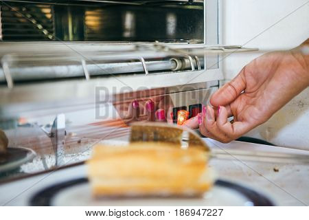 Hand of person turning on the toaster for baking a bread.