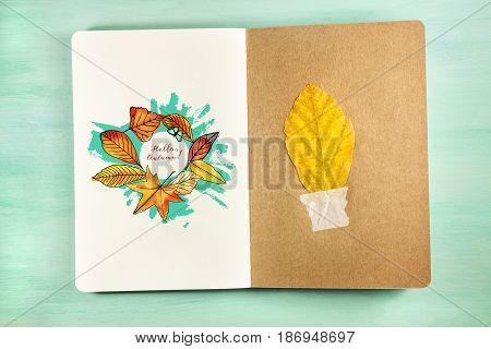 An overhead photo of a notebook with an autumn leaf taped to recycled brown kraft paper, and a drawing of autumn leaves on the other page, with a place for text, on a teal background