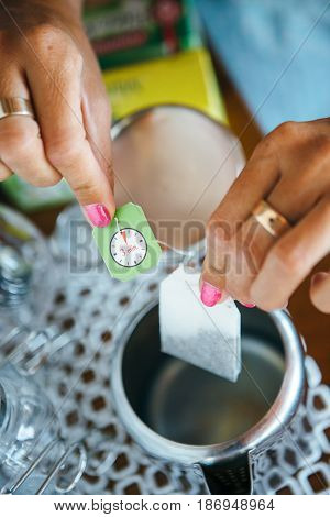 Hands of woman making a cup of tea with teabag.