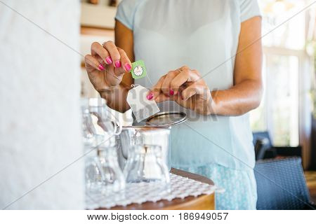 Unrecognizable woman putting the teabag to the cup making a cup of tea.